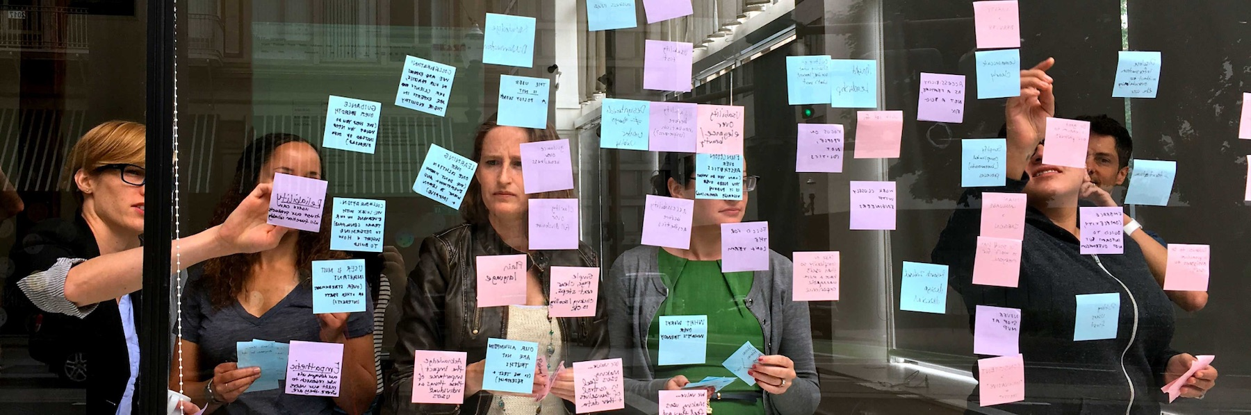 Ad Hoc staff pointing to a wall of Post-It notes on glass during an affinity mapping exercise.